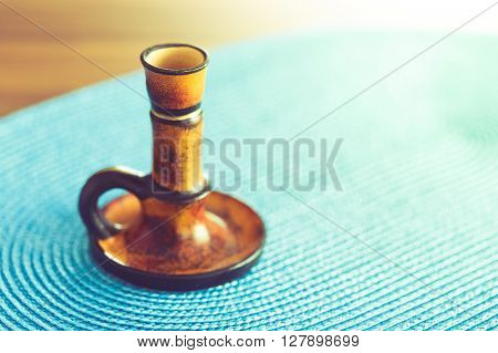 Brown candleholder on blue tablecloth with copy space. Vintage effect.