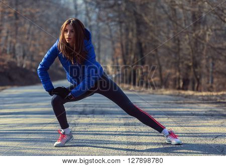 Woman warming up for morning run in nature. VIntage effect.