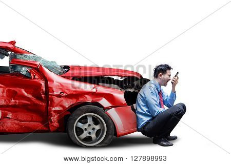Frustrated man sitting in front of a broken car after traffic accident while speaking and screaming on the cellphone