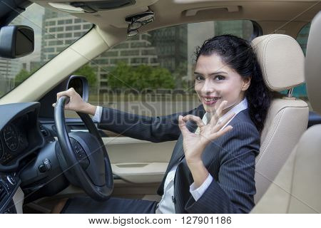 Portrait of beautiful Indian businesswoman driving a new car on the road while showing OK sign