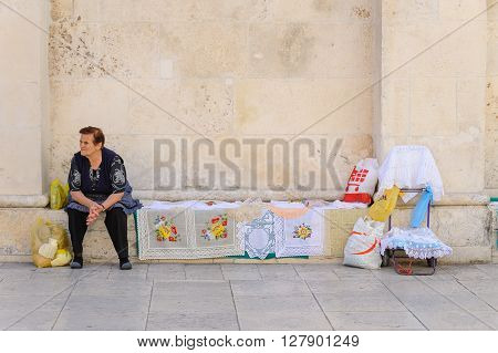 SIBENIK CROATIA - SEPTEMBER 2 2009: Local resident as a street peddler exhibiting her handicraft embroidery on the side of St. James cathedral