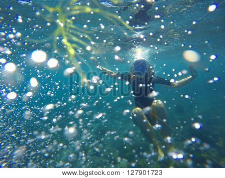 Woman snorkeling in bubbles, snorkel in blue sea, smooth silhouette of woman snorkelling, diving near coral reef, tropical sea snorkeling, summer vacation activity, girl swimming, young girl in sea
