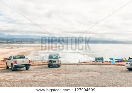 PLETTENBERG BAY SOUTH AFRICA - MARCH 3 2016: Unidentified tourists at the Whale Viewing Site with the Keurbooms River lagoon and mouth and a sandstorm in the back
