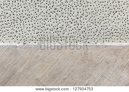 Texture of wall covered with plaster with small holes and cavities