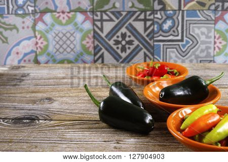 Mexican hot chili peppers colorful mix jalapeno on orange bowls and ornamental background