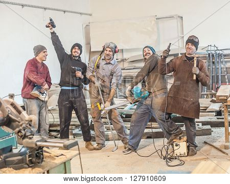 Funny Workers. Workers posing with their tools in the workshop