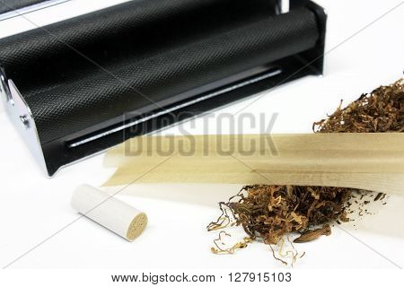 Tobacco with filter rolling machine paper isolated on white background