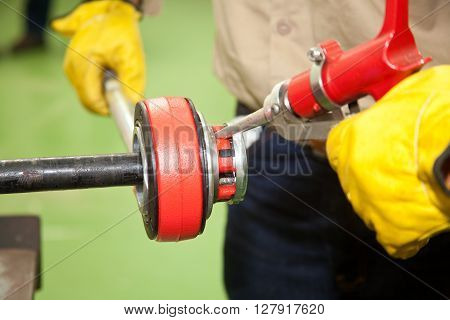 Greasing a cutting tool wearing protective gloves