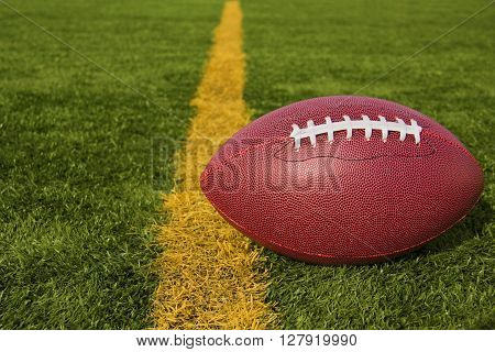 An American football resting just over the goal line for a touchdown.