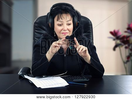 Portrait of mature physician is sitting at black wooden desk. Black haired woman wears headset because works online. She holds glasses in her hands. There are stethoscope blood pressure graphs keyboard and pen on the desk. Horizontal shot
