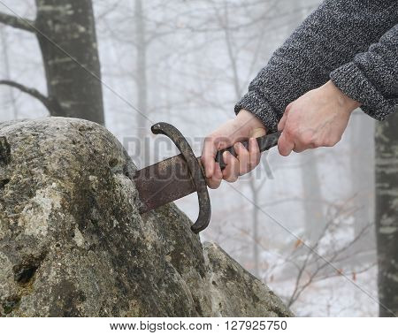 Hand of the valiant knight tries to remove the magical Excalibur sword in the stone