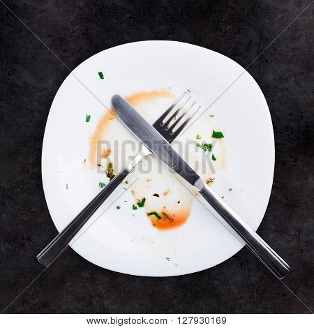 Empty plate left after dinner. Black background