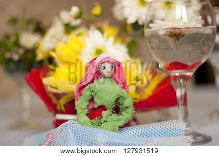 Decor for the tabletop flower arrangement. Doll with pink hair in the form of the goddess of spring. In the background a lot of flowers