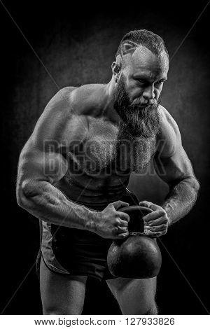 Bodybuilder With A Beard Lifts A Heavy Kettlebell.