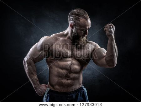 Strong man with perfect abs shoulders biceps triceps and chest. Bodybuilder topless over grunge background. poster