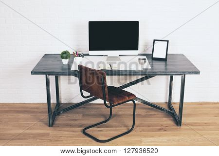 Front view of designer desk with blank computer monitor frames and other items with brown chair next to it. Wooden floor and white brick wall background. Mock up