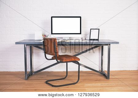 Front view of designer desk with blank computer screen frames and other items with brown chair next to it. Wooden floor and white brick wall background. Mock up