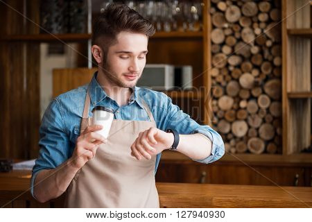 Mind the time. Pleasant handsome delighted waiter drinking coffee and looking at his wrist watch while  resting at work