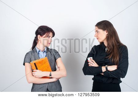Two business women standing on a light background with your arms crossed and holding a tablet and phone. Looking aggressively at each other