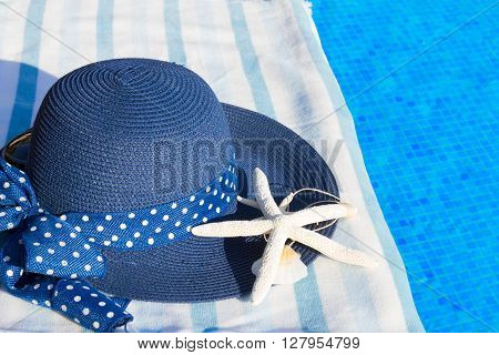 towel and summer blue hat with seashells near water of pool