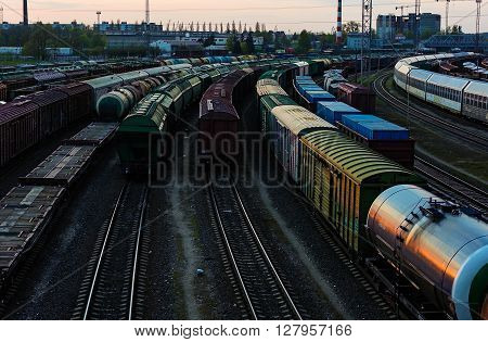 Cargo train platform at sunset with containers of oil, coal, wood ond cars. railroad. train depot