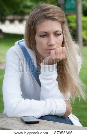 Young pensive girl on a park bench