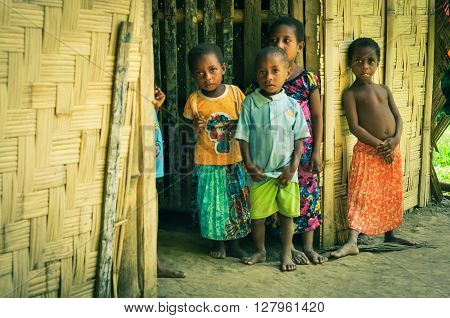 Will-will Papua New Guinea - July 2015: Small children in colourful clothes stand in house and look curiously to photocamera in Will-will Nuku Papua New Guinea. Documentary editorial.