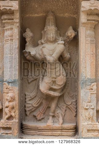 Trichy India - October 15 2013: Sandstone statue of dancing Lord Vishnu at Ranganathar Temple. Outside wall of old part built during Madurai Nayak era. He holds his discuss and conch. Statue is partly damaged.