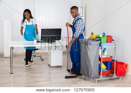 Young African Male And Female Cleaners Cleaning Office