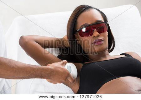 Therapist Removing Hair Of Young African Woman's Armpit With Epilator poster