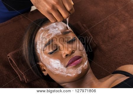 Close-up Of Young African Woman Applying Facial Mask In Spa