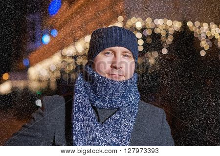 Portrait of elegant fashionable man dressed in coat and scarf.
