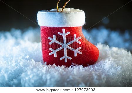 Red Santa's boot with snowflake in snow.