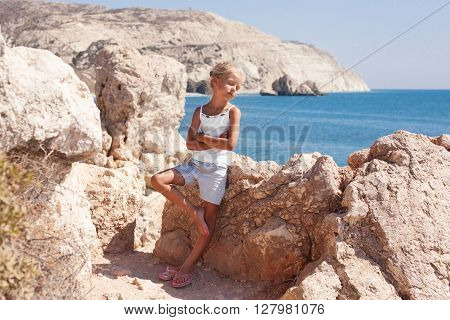 girl standing at the cliff on the seashore with her eyes shut