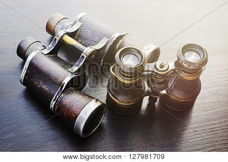 Two field glasses in a wooden background