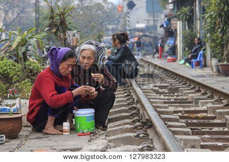 Hanoi, Vietnam - February 19, 2016: Old Women Eating On The Railway In The Center Of Hanoi