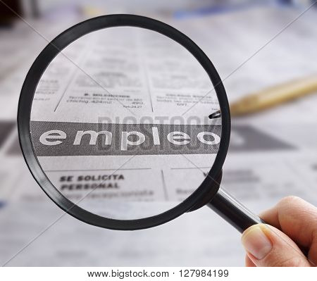 Person looking at employment section of a Spanish language newspaper