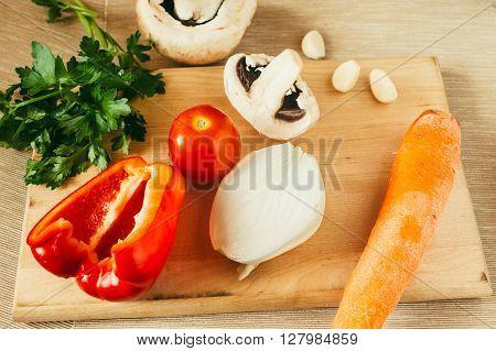Set of vegetables for salad on wooden board