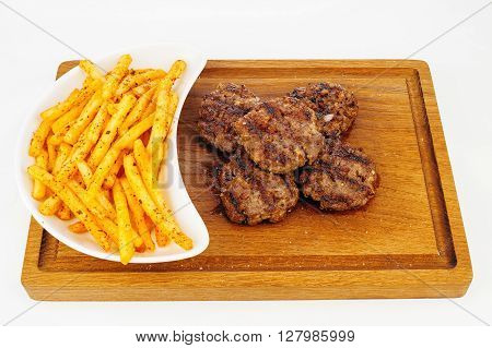 Grilled beef cutlets with french fries on wooden plate
