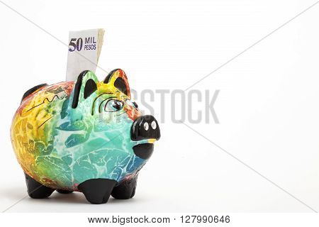 Saving colombian money in a Colorful piggy bank -  side view