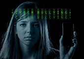 young scared and worried teenager girl holding mobile phone as internet stalked victim abused and cyberbullying or cyber bullying stress concept in computer text code black background poster