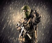 Close up of an armed terrorist man with mask on rainy background poster