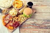 fast food and unhealthy eating concept - close up of fast food snacks and cola drink on wooden table poster
