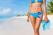 Sexy bikini body woman - abs, sunglasses, flip flops on beach vacation. Model showing slim abs and tanned skin on tropical caribbean travel destination vacation. Belly button stomach and thighs legs. poster