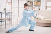 Beautiful woman doing qi gong tai chi exercise or reiki wearing professional, original Chinese clothes at home poster