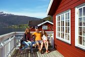 happy family sitting near rorbu. beautiful Norwegian landscape at the fjord and mountains norway poster