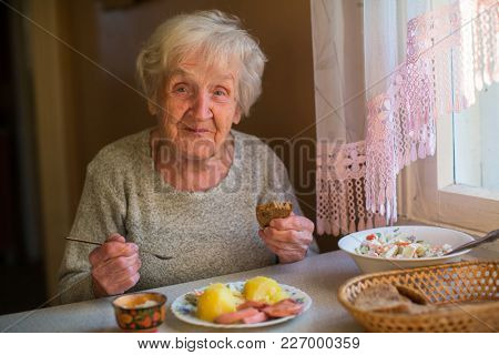 Older woman eating at home at the table.