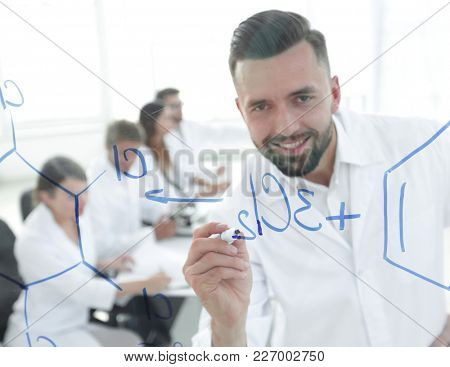 close up of a smiling scientist writes a formula on the blackboard