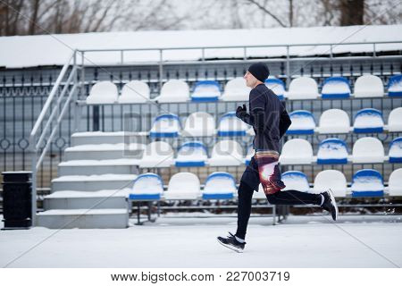 Photo of running sportsman in stadium at winter