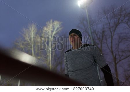 Photo of sports man pulling up on bar in evening at moon